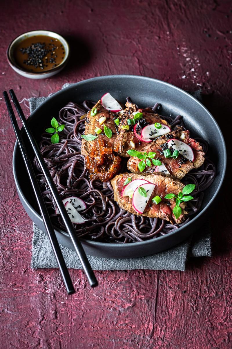ciotola con noodle di riso nero e tataki di manzo