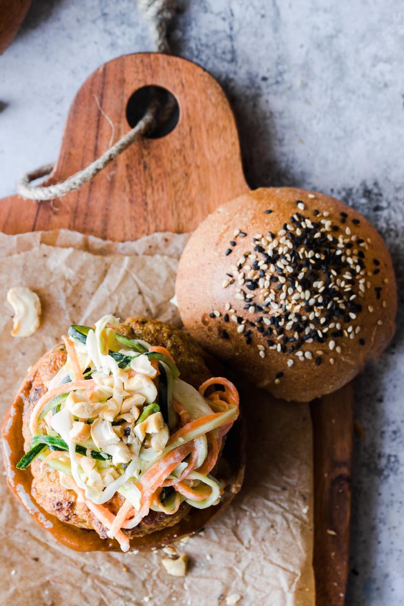 Tagliere con panino ai semi di sesamo aperto con burger di tacchino e coleslaw sopra