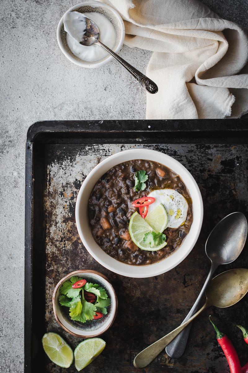 Ciotole di zuppa di fagioli neri e patata dolce con coriandolo e lime