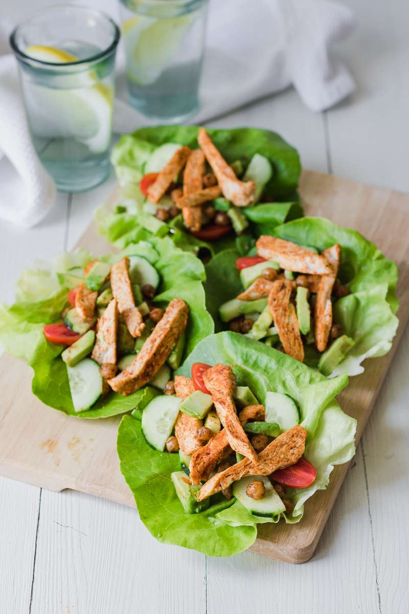 Wrap di lattuga con pollo alla greca, insalata di cetrioli e pomodori, avocado e ceci