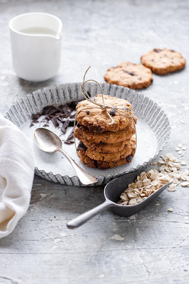 Pila di biscotti all'avena e cioccolato in un vassoio bianco con accanto cioccolato e latte