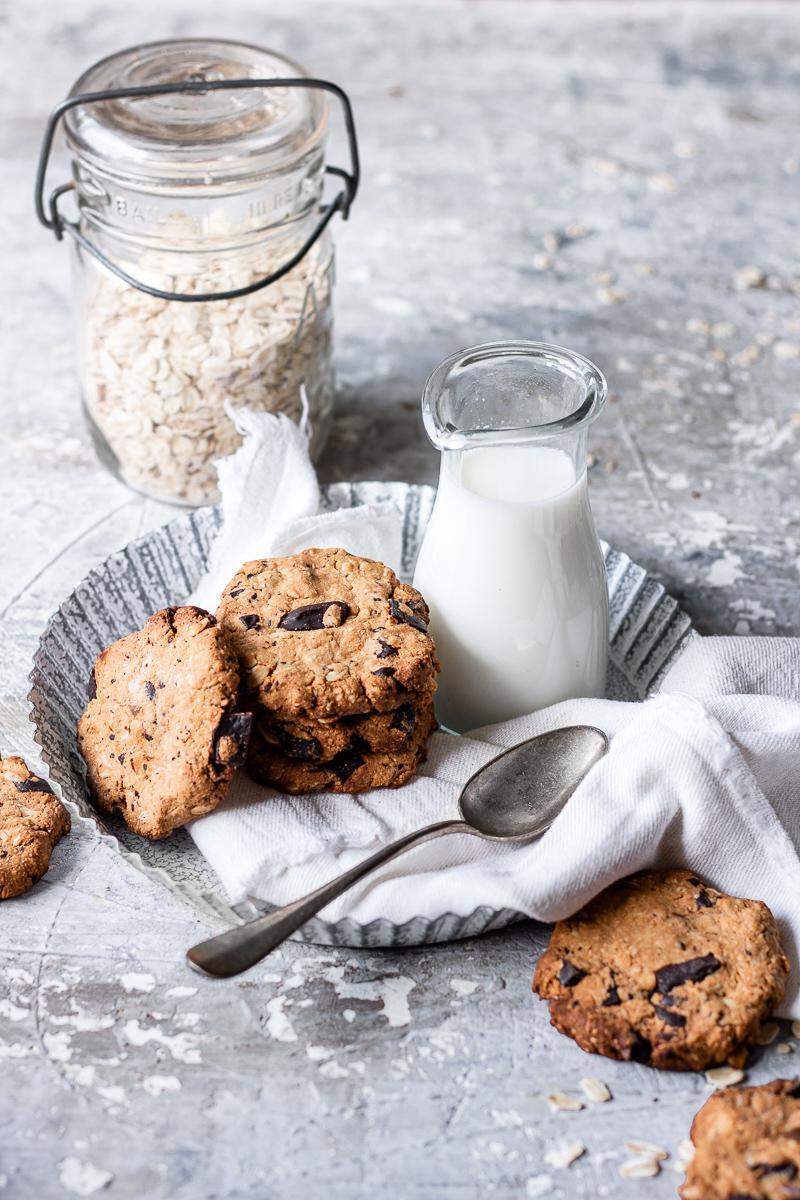 Biscotti all'avena e cioccolato senza glutine e senza burro appoggiati su un vassoio bianco con un bricco di latte