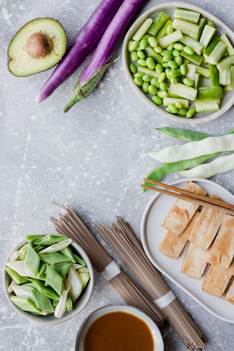 Ingredienti per l'insalata di soba: taccole, avocado, tofu, melanzane perline, edamame