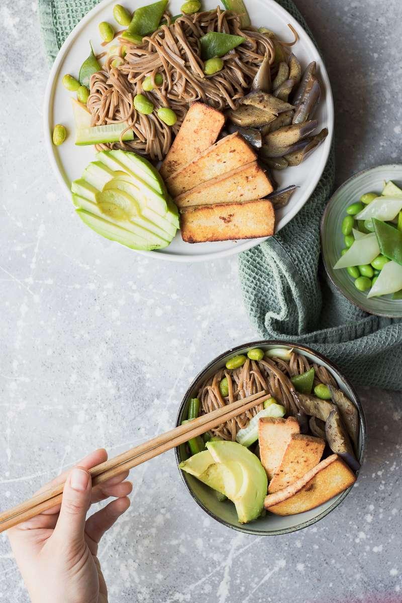 Insalata di soba fredda con salsa alla tahina, tofu affumicato, melanzane e avocado