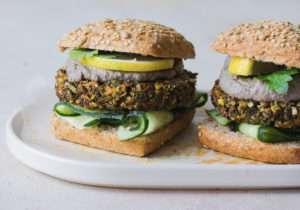 Due panini con veg burger di quinoa, patata dolce, fave con salsa tofu e olive visti di profilo