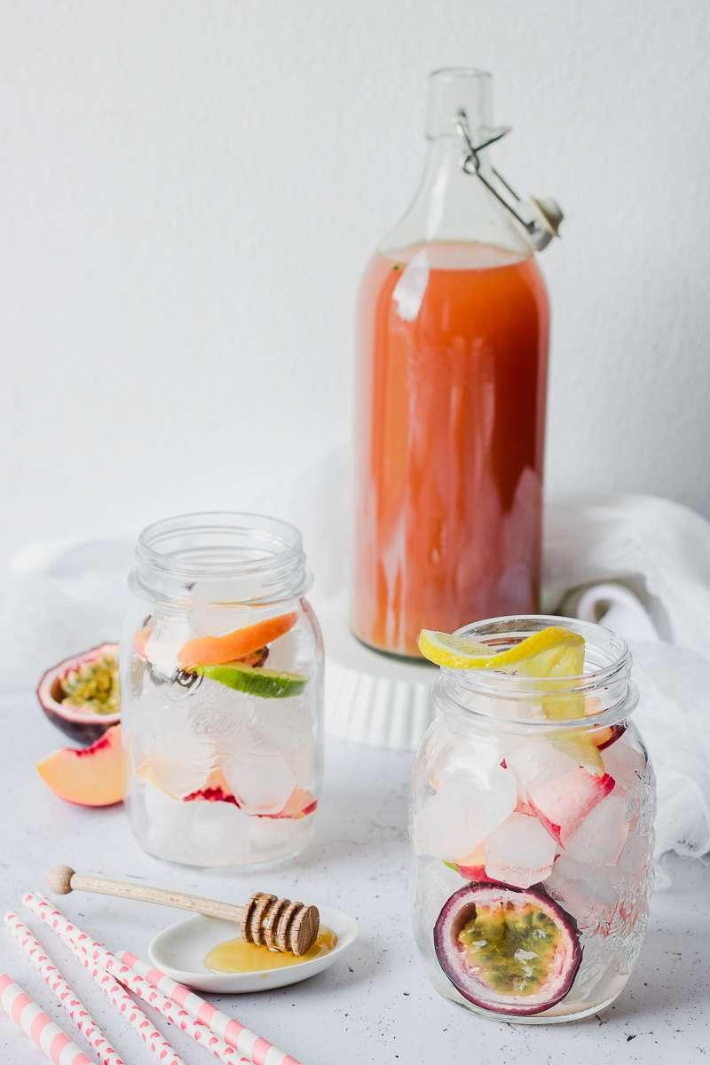 Bottiglia di tè freddo alle pesche e frutto della passione pronta per essere versata