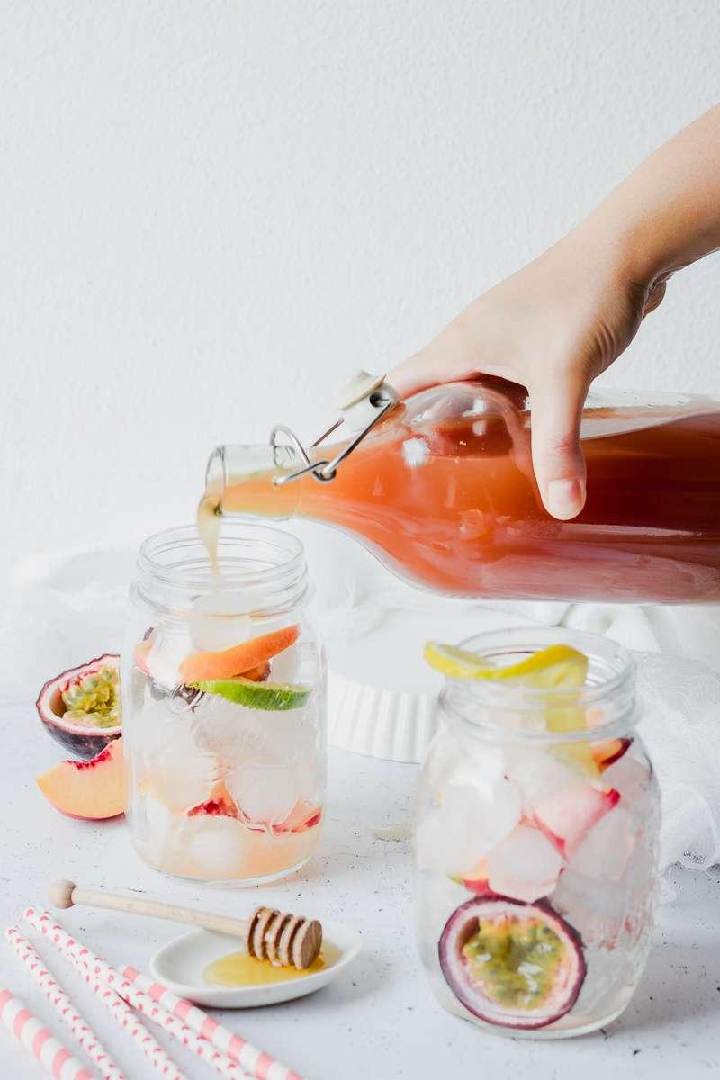 Mano che versa una bottiglia di tè freddo alle pesche e frutto della passione