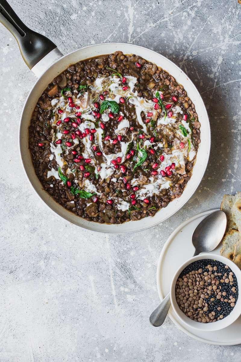 Pentola di stufato di lenticchie in stile mediorientale con yogurt e melograno