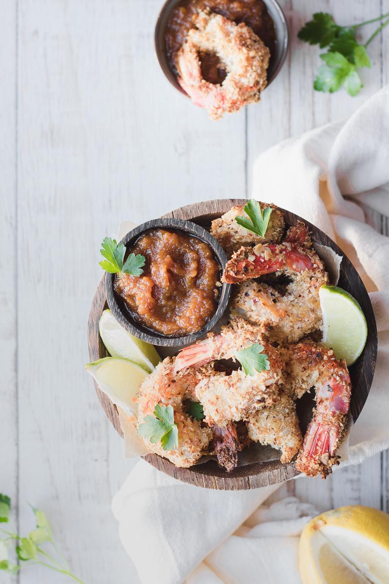 Ciotola di legno con gamberi impanati low carb e piccola ciotola con dentro finta salsa barbecue, tutto cosparso di prezzemolo, con fettine di agrumi