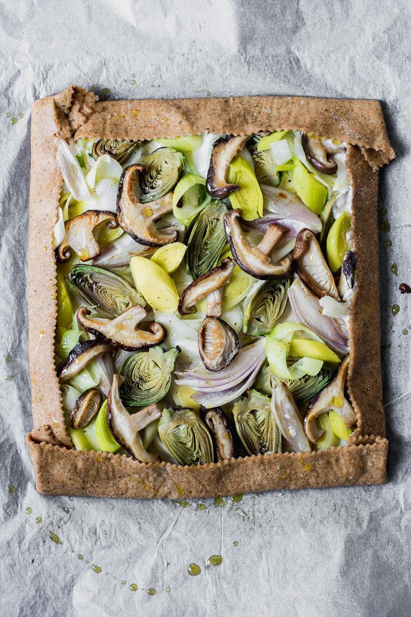 Torta salata integrale senza burro nell'impasto ricoperta di porri, funghi shitake, scalogno e carciofini, cruda pronta per essere cotta