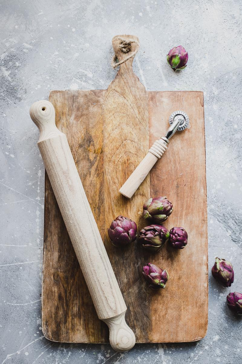 Tagliere con mattarello carciofini e taglia pasta