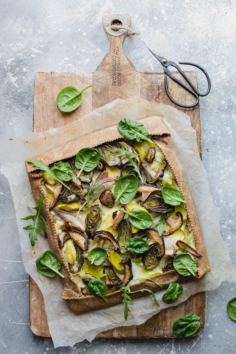 Torta salata integrale senza burro ai porri, funghi shitake e carciofini, con foglie di spinacino e rucola su un tagliere con un paio di forbici