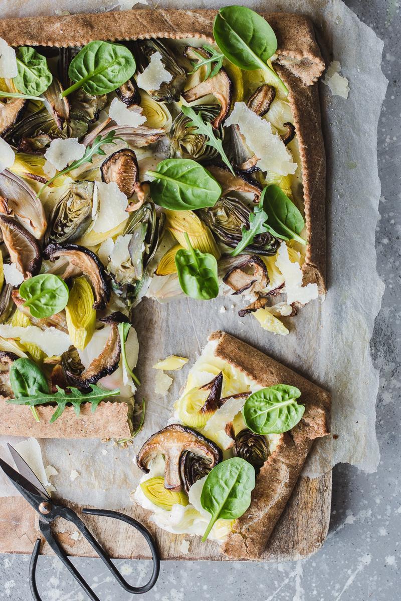 Torta salata integrale senza burro ai porri, funghi shitake e carciofini, con foglie di spinacino e rucola con un paio di forbici e una fetta già tagliata, su un tagliere di legno
