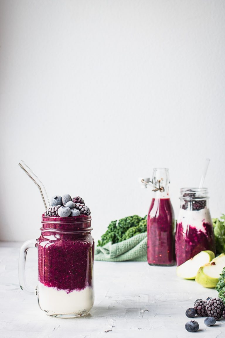 Tre bicchieri di vetro con dentro un frullato viola di verdura e frutta variegato allo yogurt, con foglie di verdura sparse sul tavolo