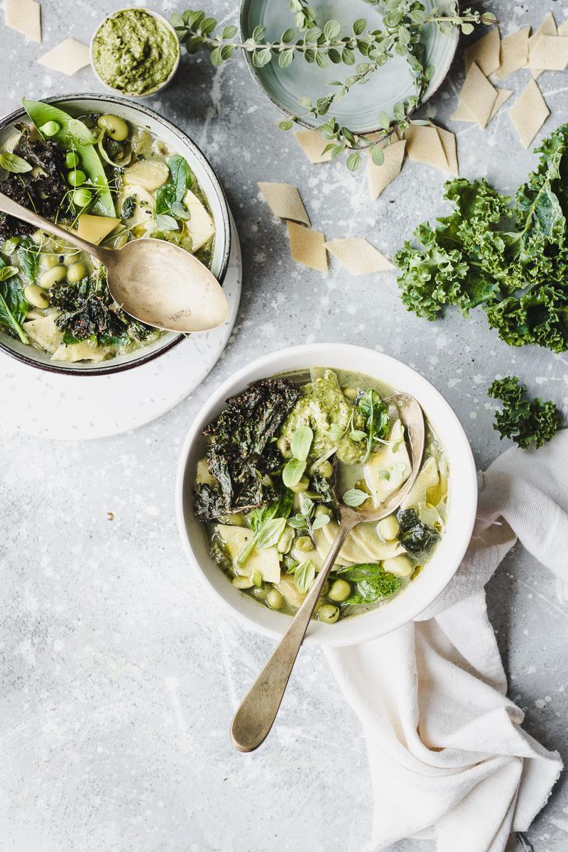 Due ciotole con minestrone verde con legumi verdure e maltagliati, con cucchiai e foglie sparse, visto dall'alto