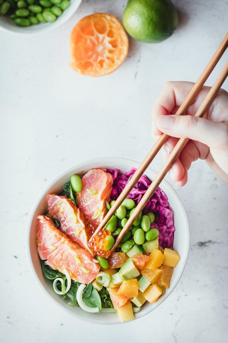 Bowl low carb di salmone in salsa ponzu con cavolo cappuccio viola sott'aceto, edamame, verdura e insalata di avocado, mango e arancia