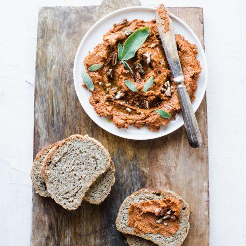 Patè di pomodori secchi vegano con salvia e noci e fette di pane di segale su tagliere