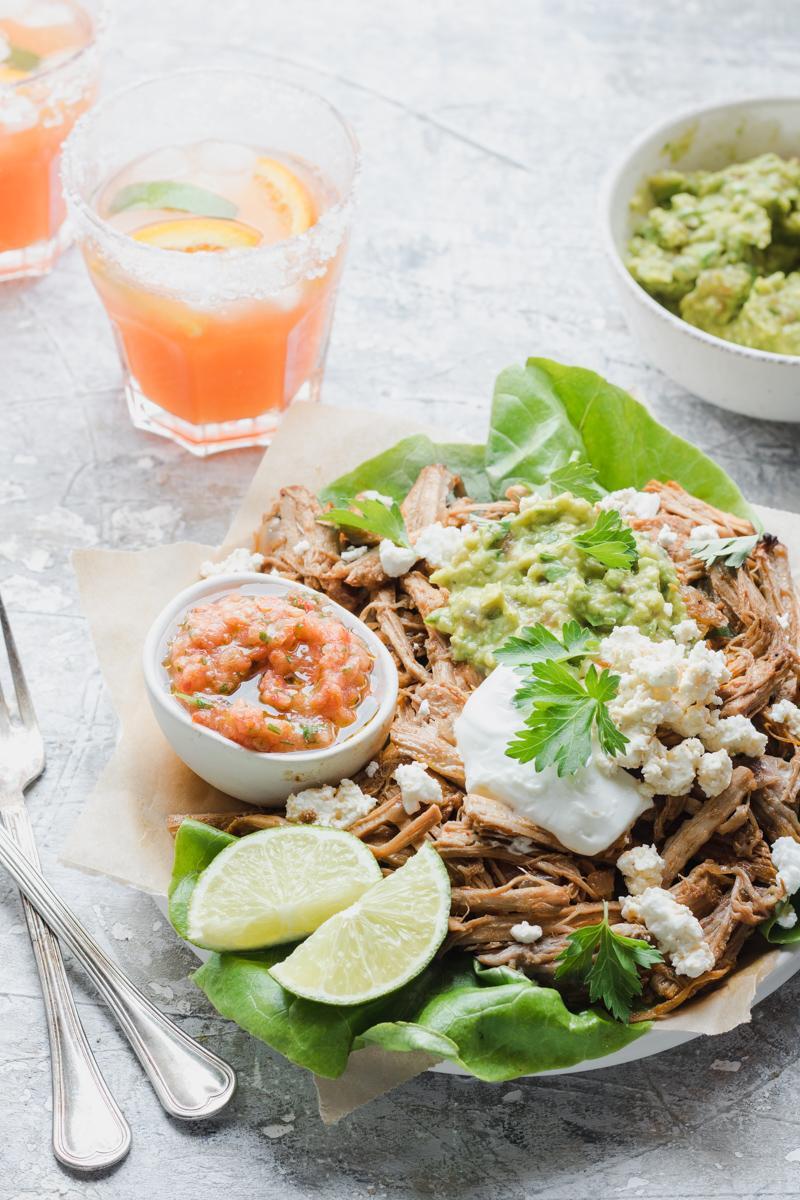 Piatto di carnitas con salsa, ciotola di guacamole e due bicchieri di margaritas in controluce