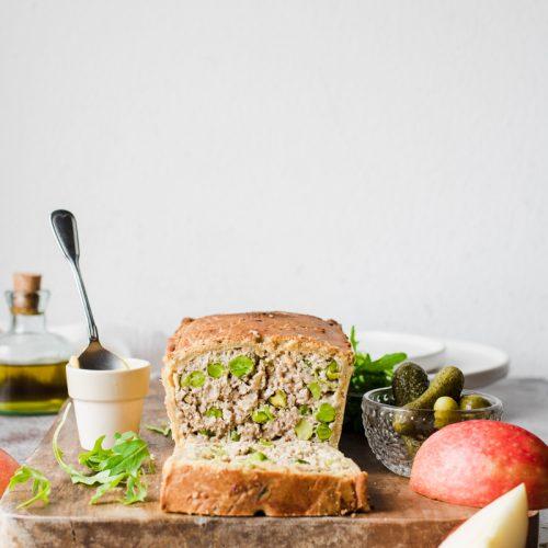 Terrina di maiale in crosta, con pistacchi e piselli, già affettata su un tagliare di legno con mele, sottaceti, rucola e senape