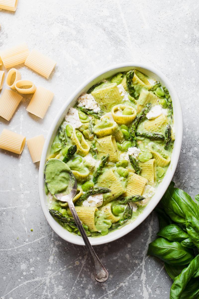 Teglia di pasta al forno vegetariana con asparagi, fave, basilico e burrata pronta per il forno