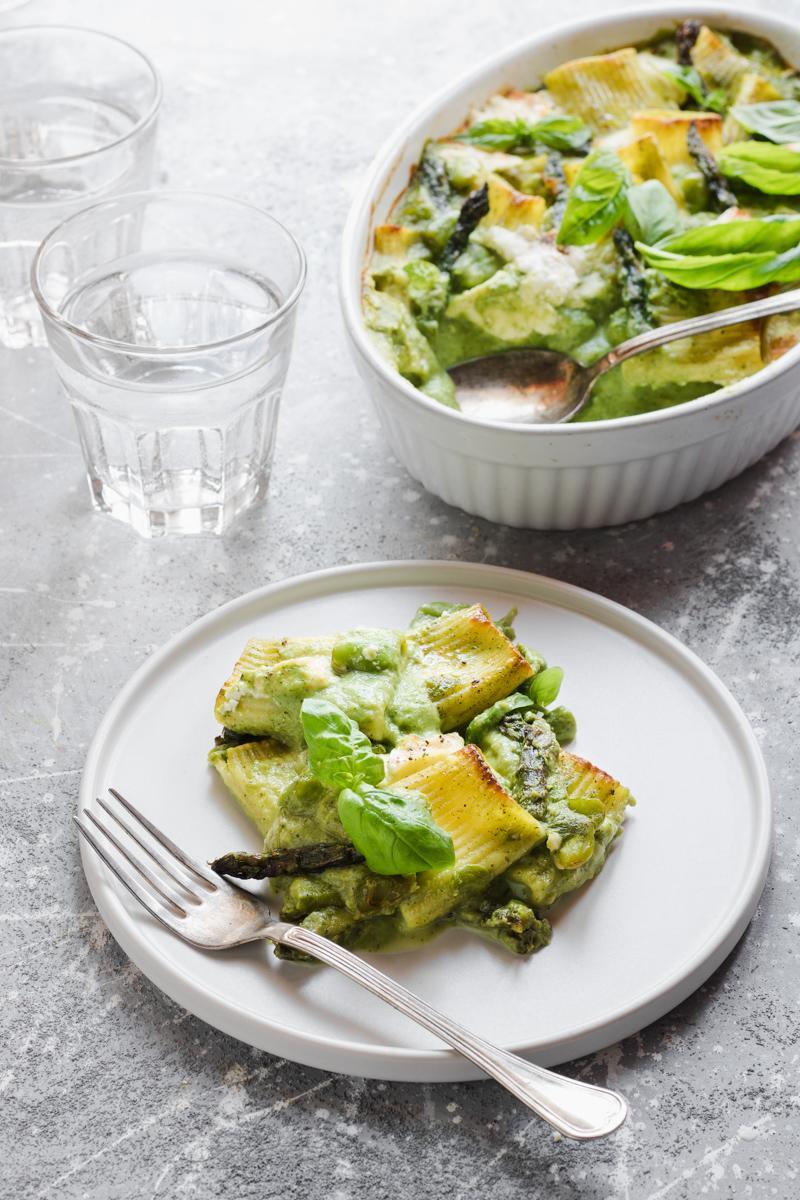 Piatto di pasta al forno agli asparagi, fave e burrata affumicata