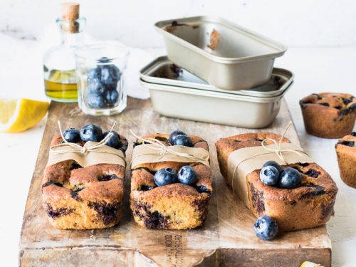 Mini plumcake ai mirtilli e limone con olio extravergine su un tagliere con gli stampi