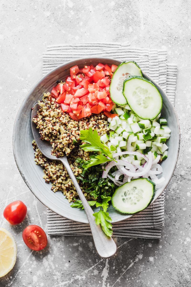 Ciotola con cucchiaio e quinoa tricolore, cetrioli, prezzemolo, pomodoro, cipolla rossa