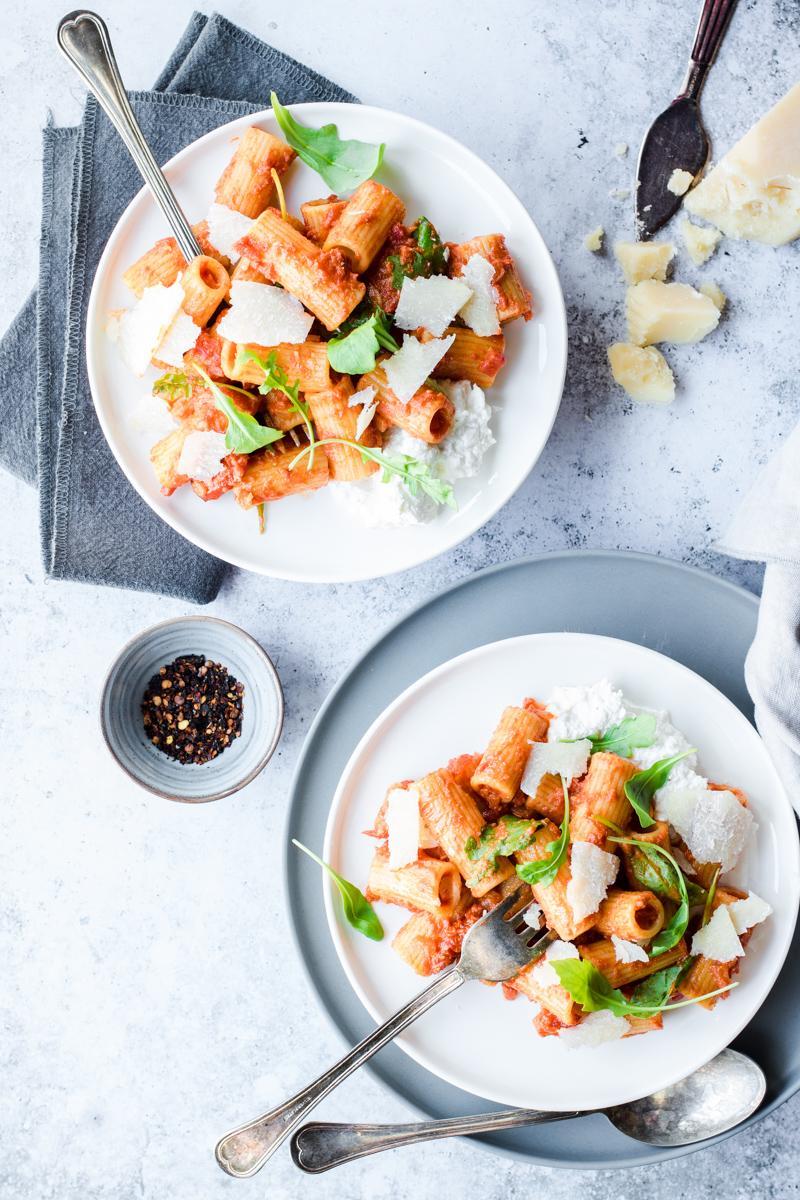 Due piatti di rigatoni all'amatriciana ma senza guanciale nè pancetta, con rucola, pomodorini, ricotta e parmigiano