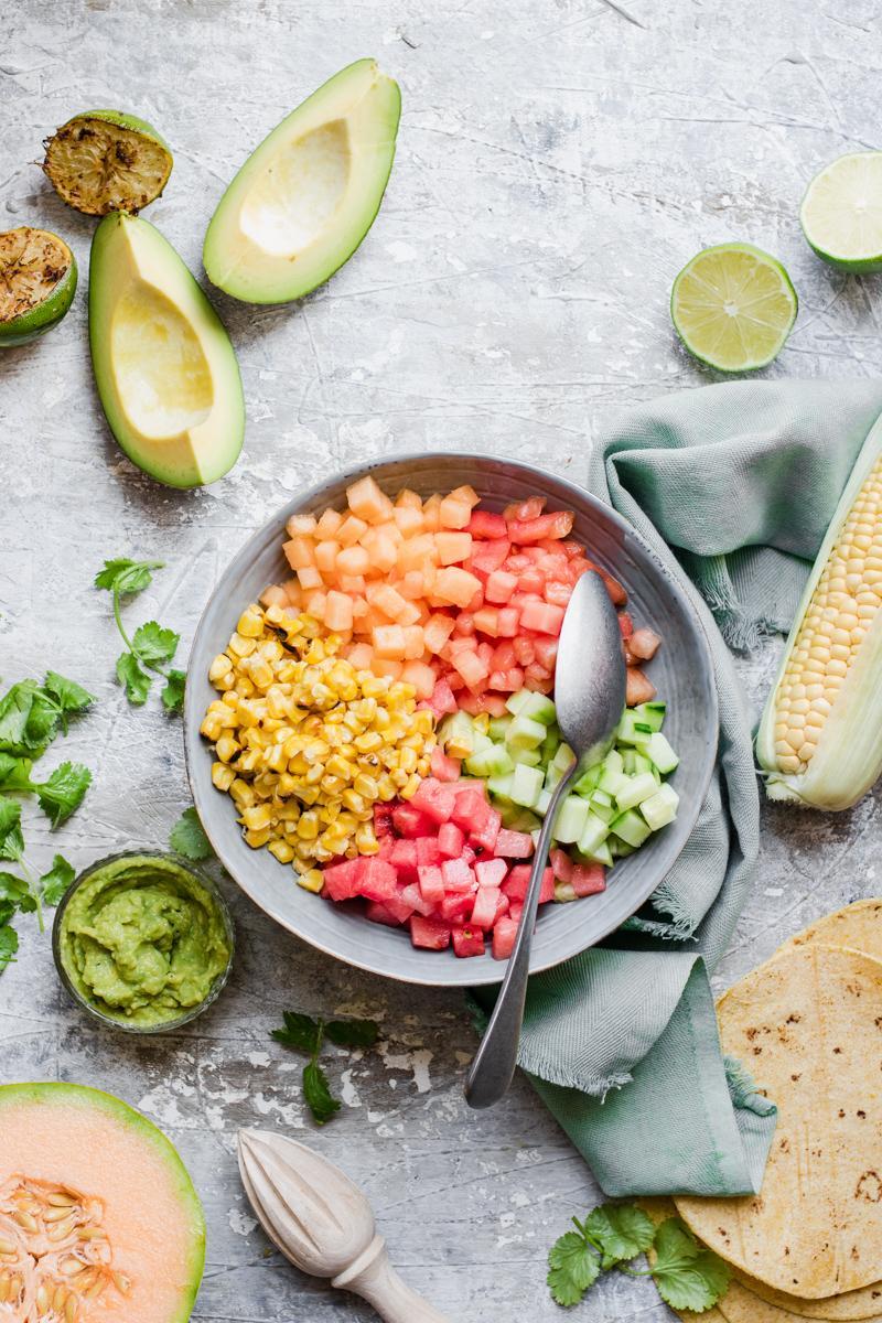 Ciotola con melone, anguria, mais, cetrioli e pomodori tagliati a dadini per la salsa messicana