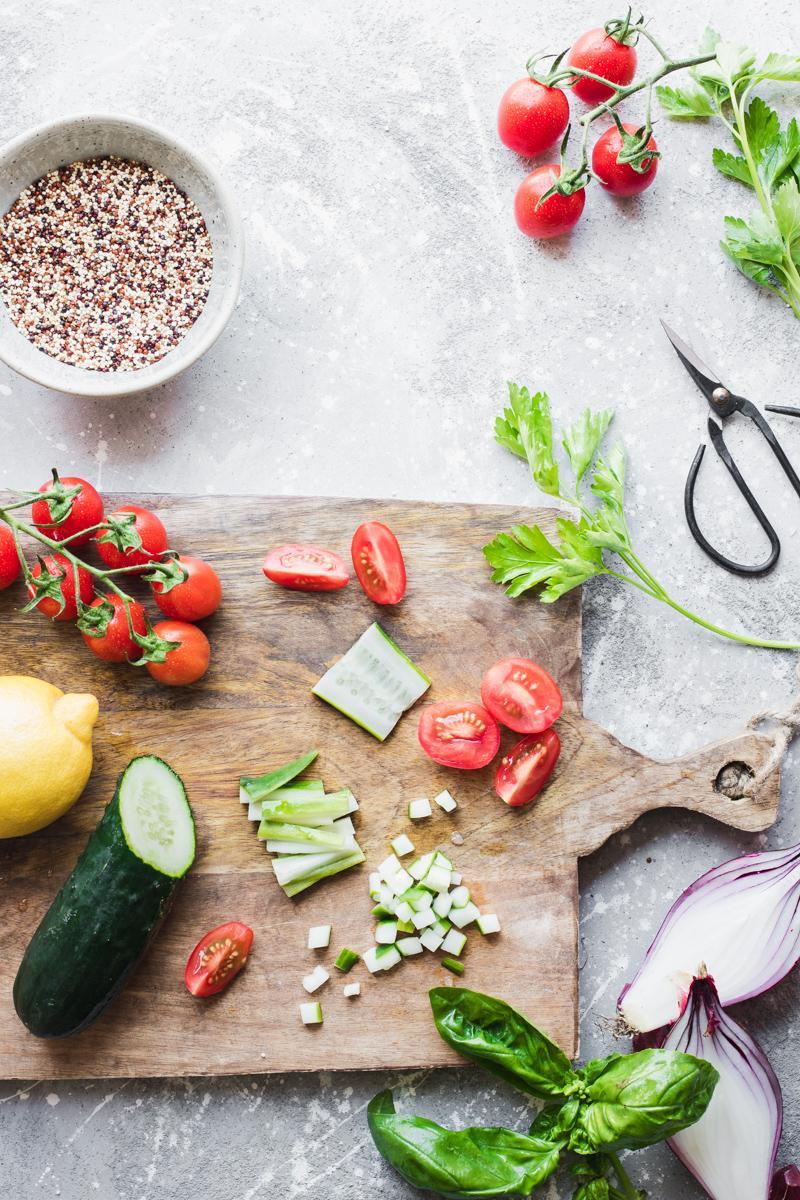 Tagliere di legno con pomodori, cetrioli, limone, erbe aromatiche, cipolla rossa e ciotolina con quinoa tricolore cruda