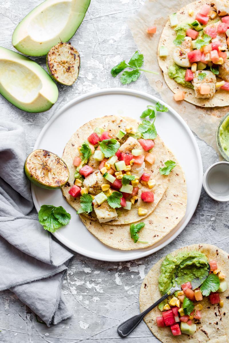 Taco di halibut aperto con salsa, foglie di coriandolo e lime spremuto
