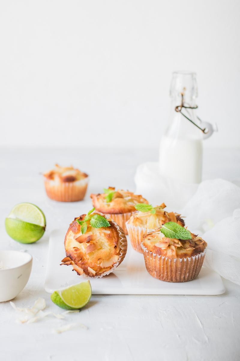 Muffin al cocco e ananas su un tagliere di ceramica bianca con un lime tagliato e bottiglia di lette sullo sfondo