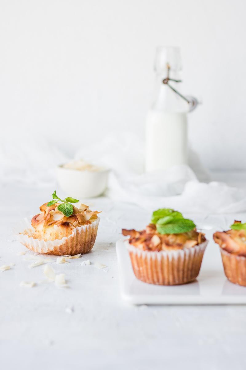 tre muffin nei pirottini di carta decorati con foglie di menta con una bottiglietta di vetro di latte sullo sfondo