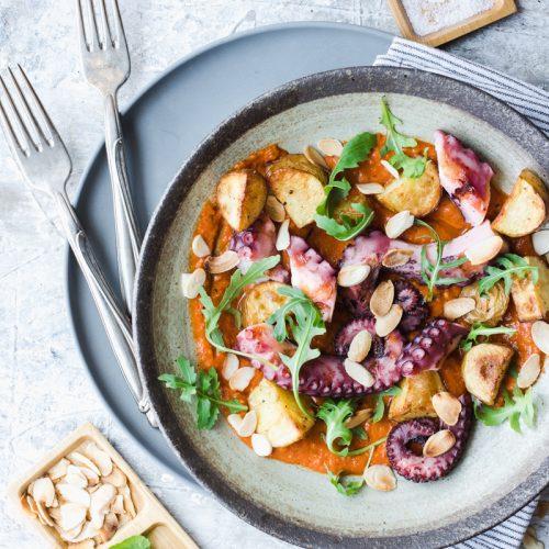 Piatto di polpo con patate arrosto, rucola e salsa romesco