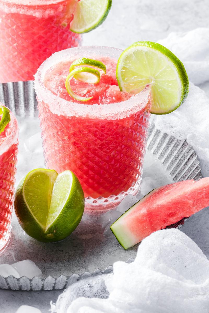 Un bicchiere con drink all'anguria con fetta di lime, lime aperto a fianco e fetta di anguria