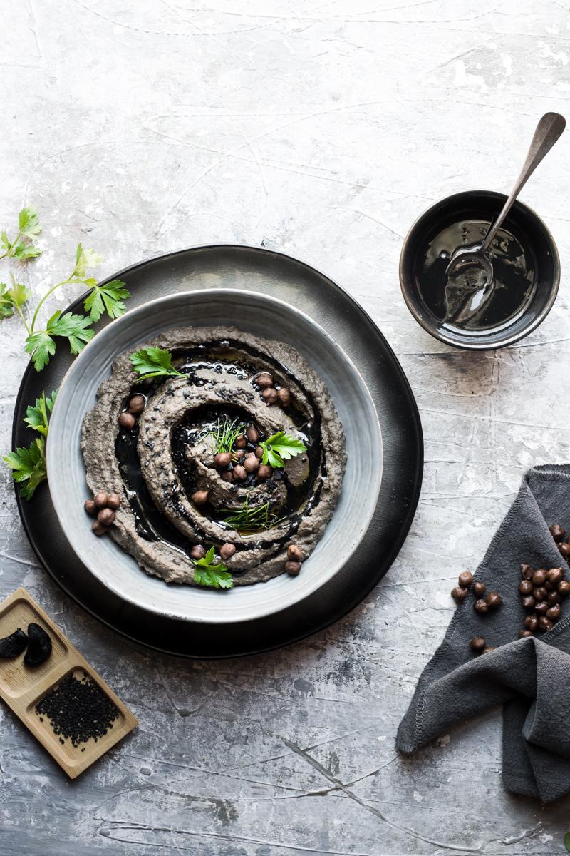 ciotola di hummus nero con foglie di prezzemolo