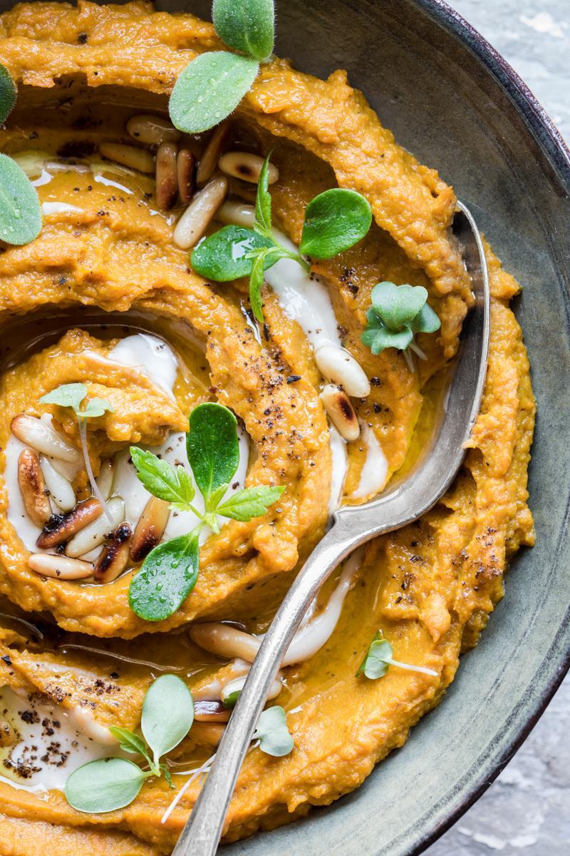 close up di hummus di zucca e carote al miso con tahine e pinoli