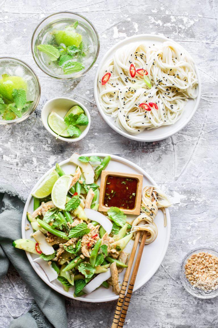 Piatto con verdure verdi, insalata di pollo, bacchette con noodle avvolti e piattino quadrato di salsa di soia, accanto a un piatto di noodle e un bicchiere di mojito analcolico