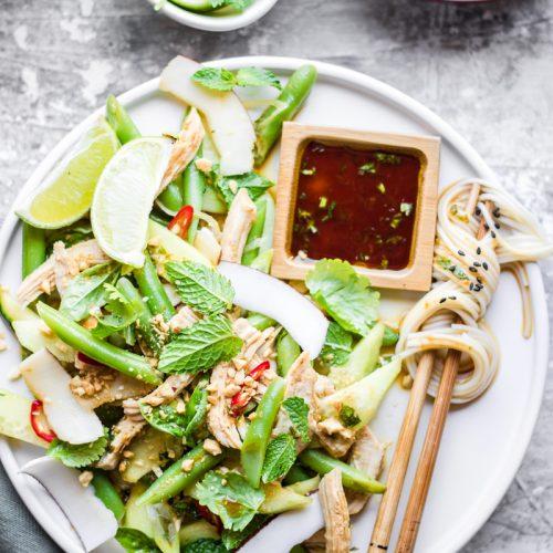 Piatto con verdure verdi, menta, lime e cocco, nsalata di pollo, bacchette con noodle avvolti e piattino quadrato di salsa di soia