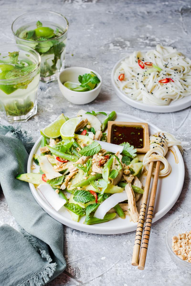 Piatto con verdure verdi, insalata di pollo, bacchette con noodle avvolti e piattino quadrato di salsa di soia