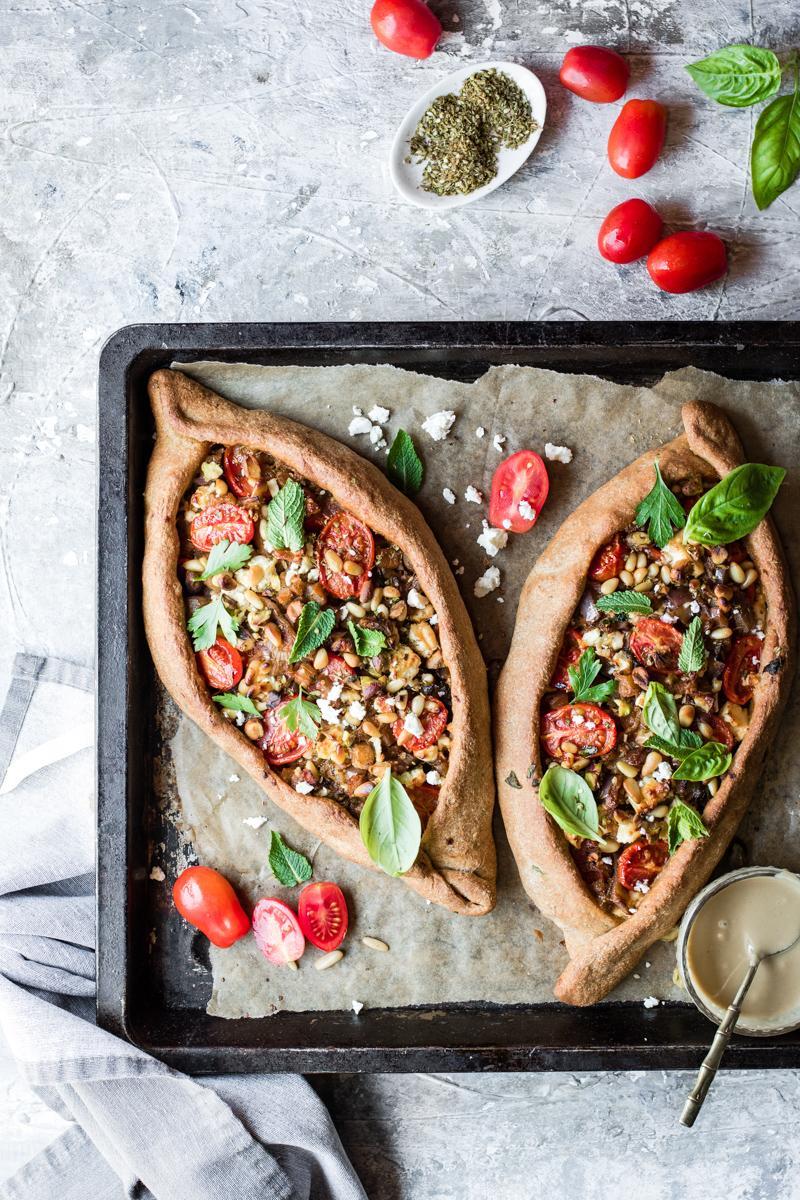 Teglia da forno con due turkish pide con pomodorini, feta e erbe aromatiche