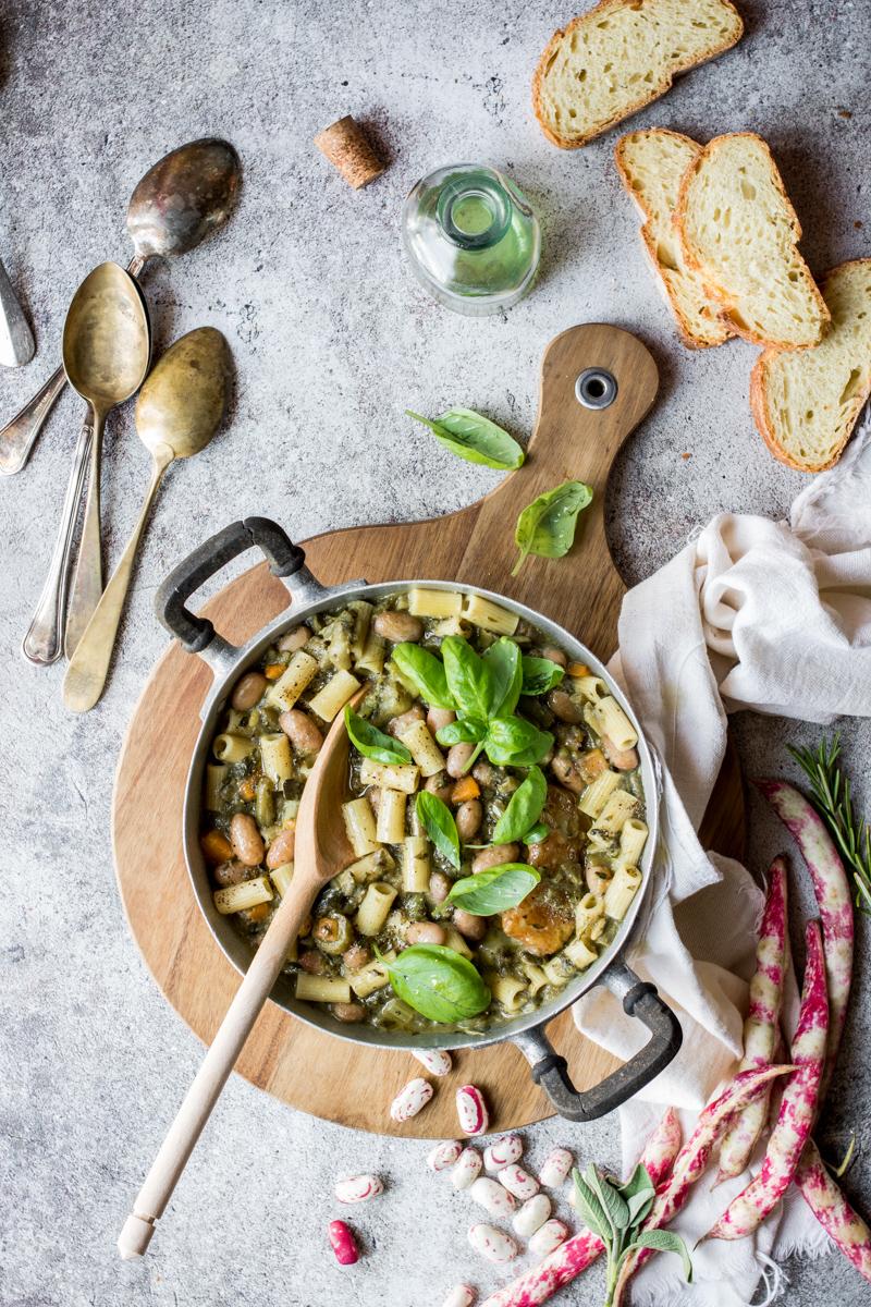 pentola di minestrone con basilico su tagliere con strofinaccio e cucchiai