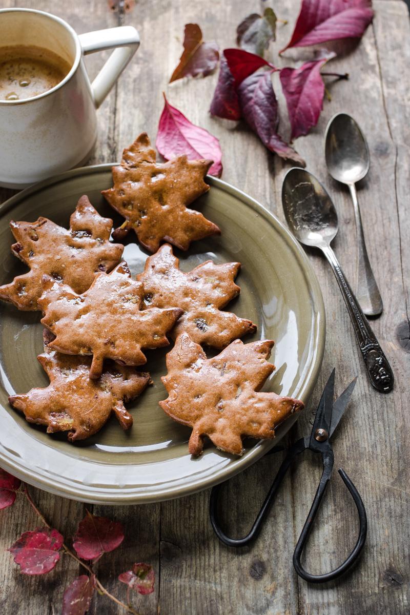 biscotti di farina di castagne a forma di foglia su un piatto con attorno foglie e una tazza di caffè