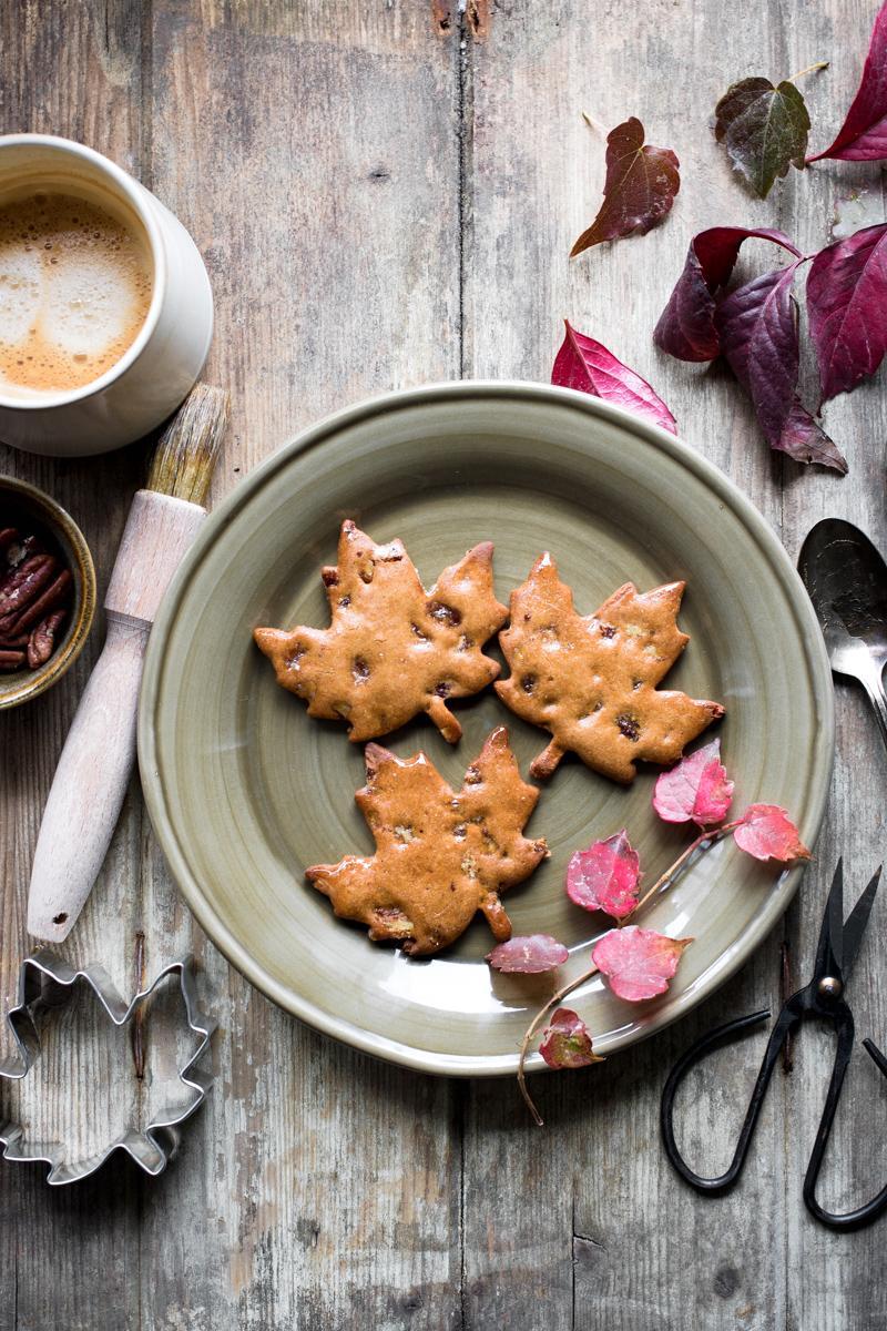 tre biscotti di farina di castagne e sciroppo d'acero senza glutine a forma di foglia su un piatto visto dall'alto con attorno foglie autunnali e un caffè