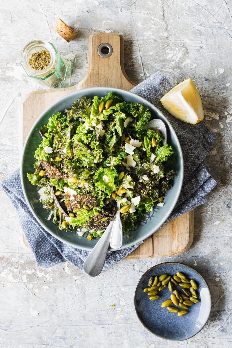 Piatto con insalata di kale o cavolo riccio su tagliere con limone e pistacchi in una ciotolina