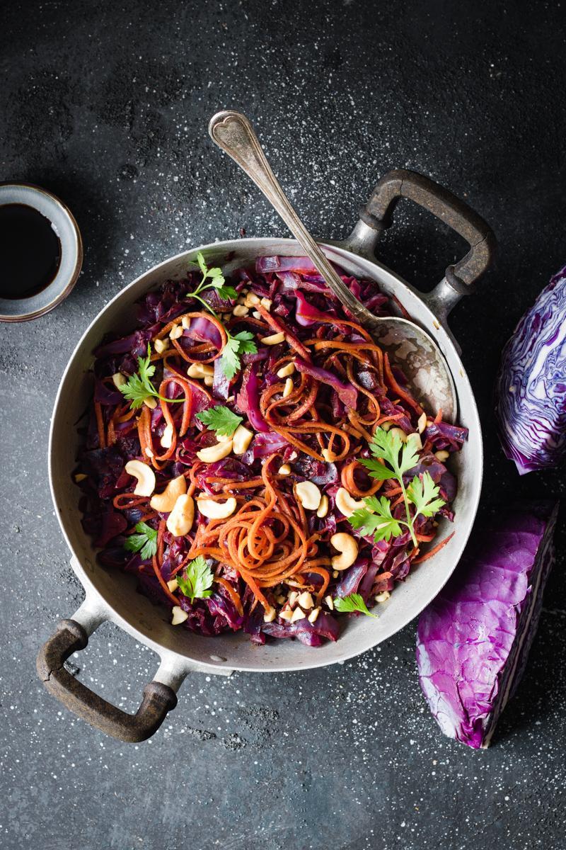cavolo viola stufato con carote, anacardi e spezie in un pentolino di acciaio su sfondo scuro