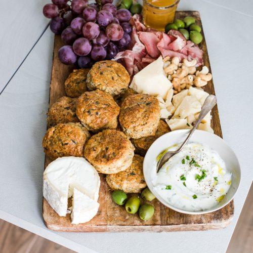 tagliere con scones salati salumi, formaggi, uva e ciotola con panna acida