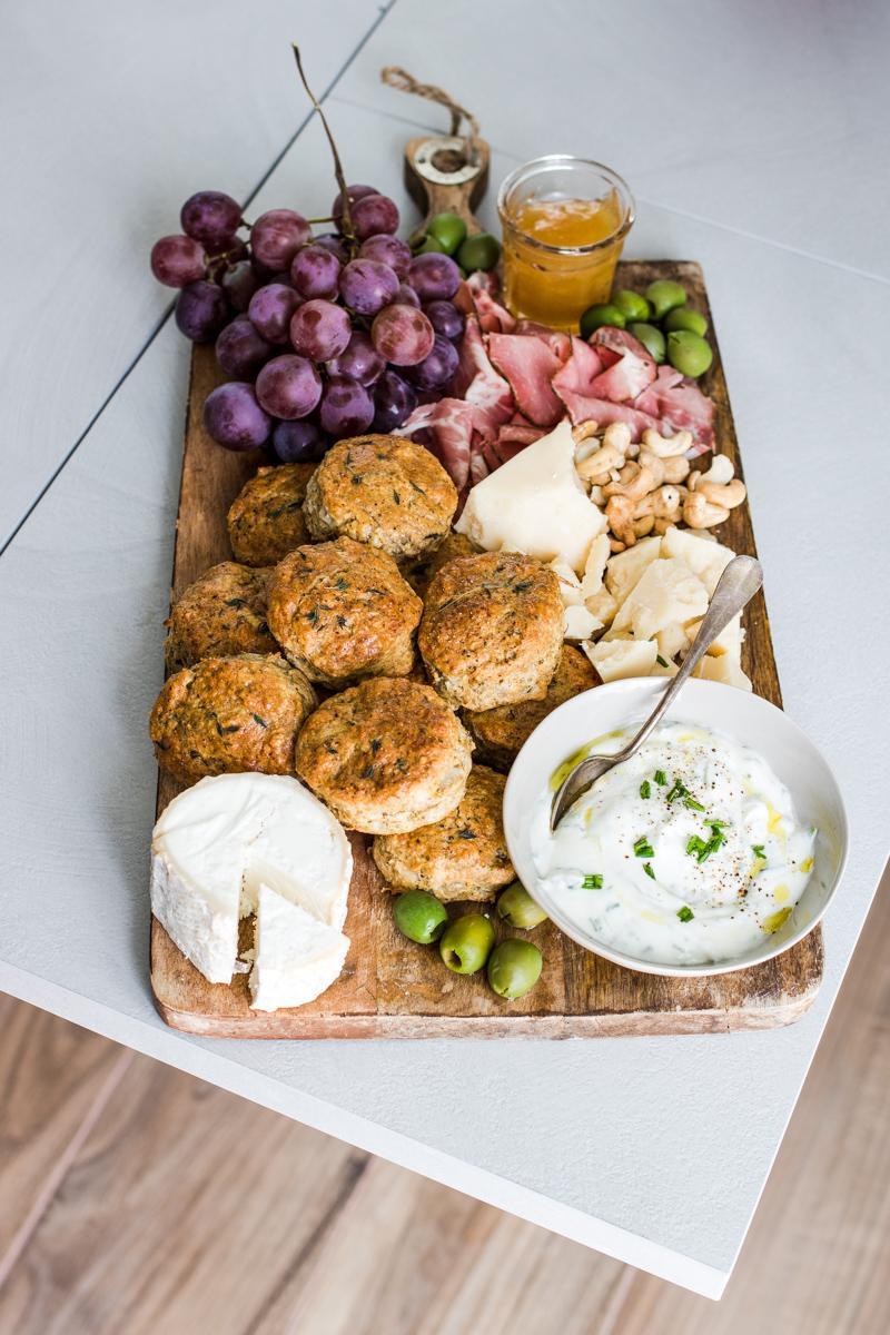 tagliere comn scones salati salumi, formaggi, uva e ciotola con panna acida