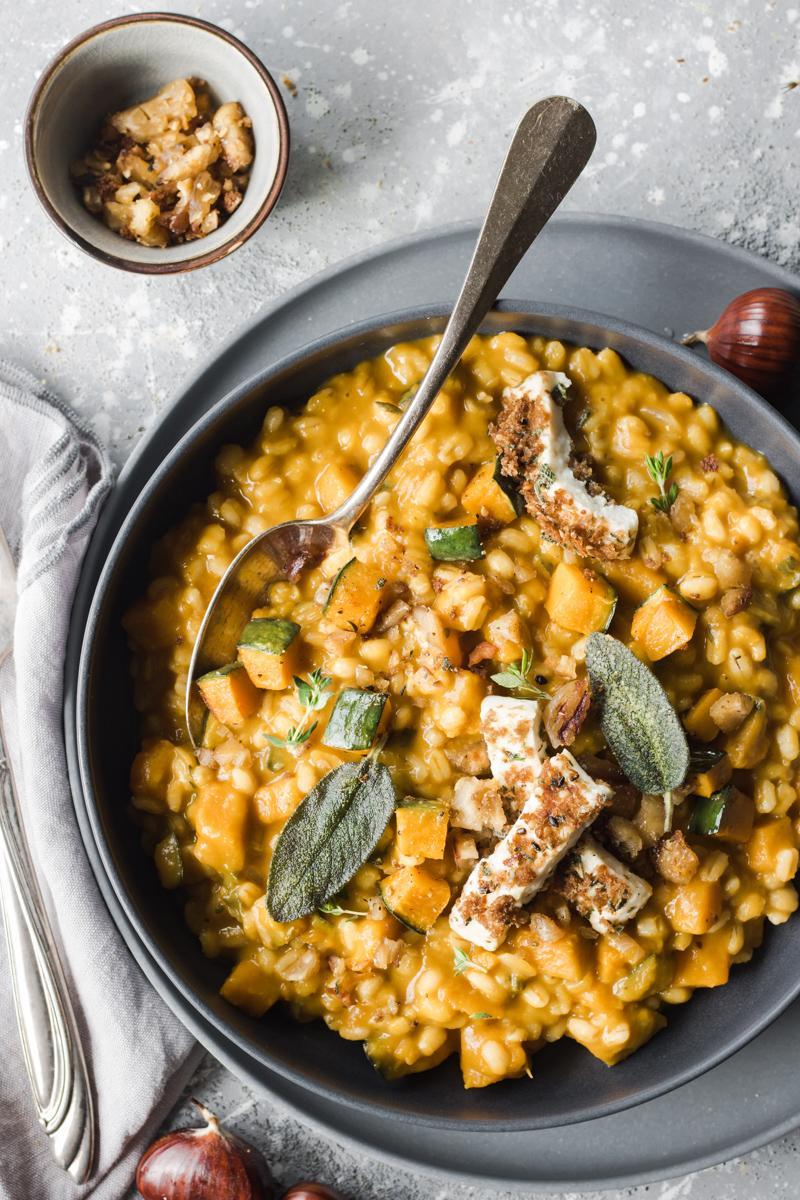 Piatto di orzotto alla zucca e castangne con primosale e foglie di salvia con cucchiaio infilato nel piatto