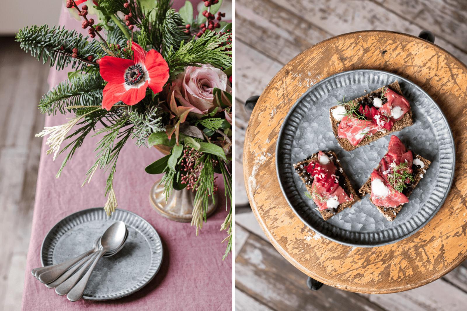 Piatto zincato con tartine di pane nero, e piatto zincato su tovaglia borgogna con vaso di fiori